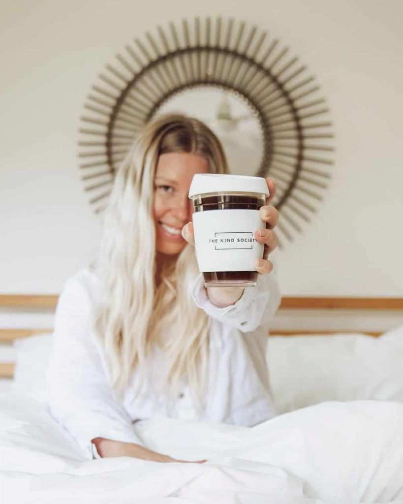 Brand image of Gina holding Kind society reusable coffee cup in bed
