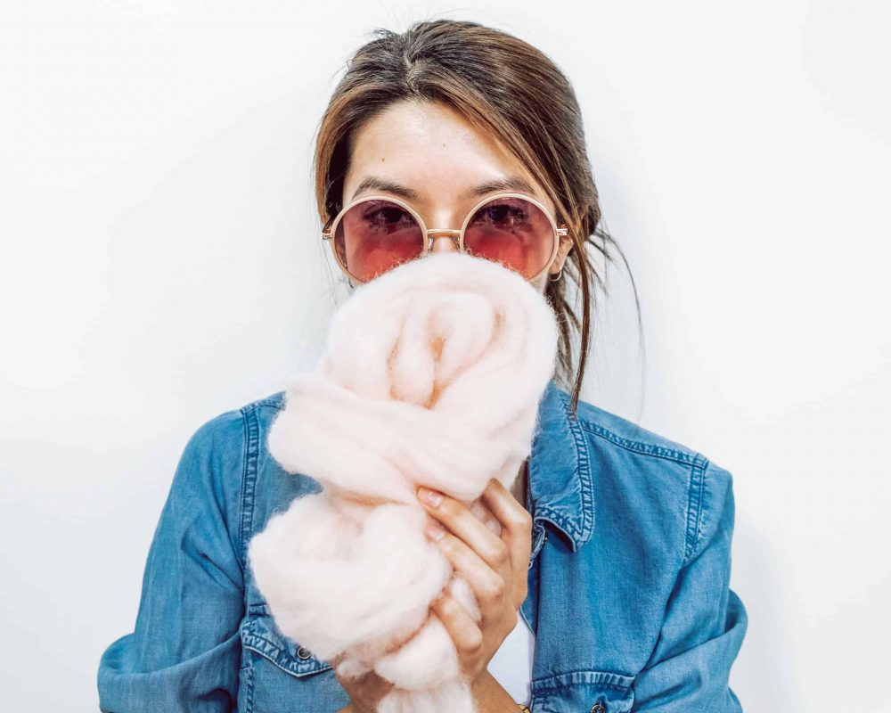 Brand image of Rachel wearing big round sunglasses holding fluffy pink yarn