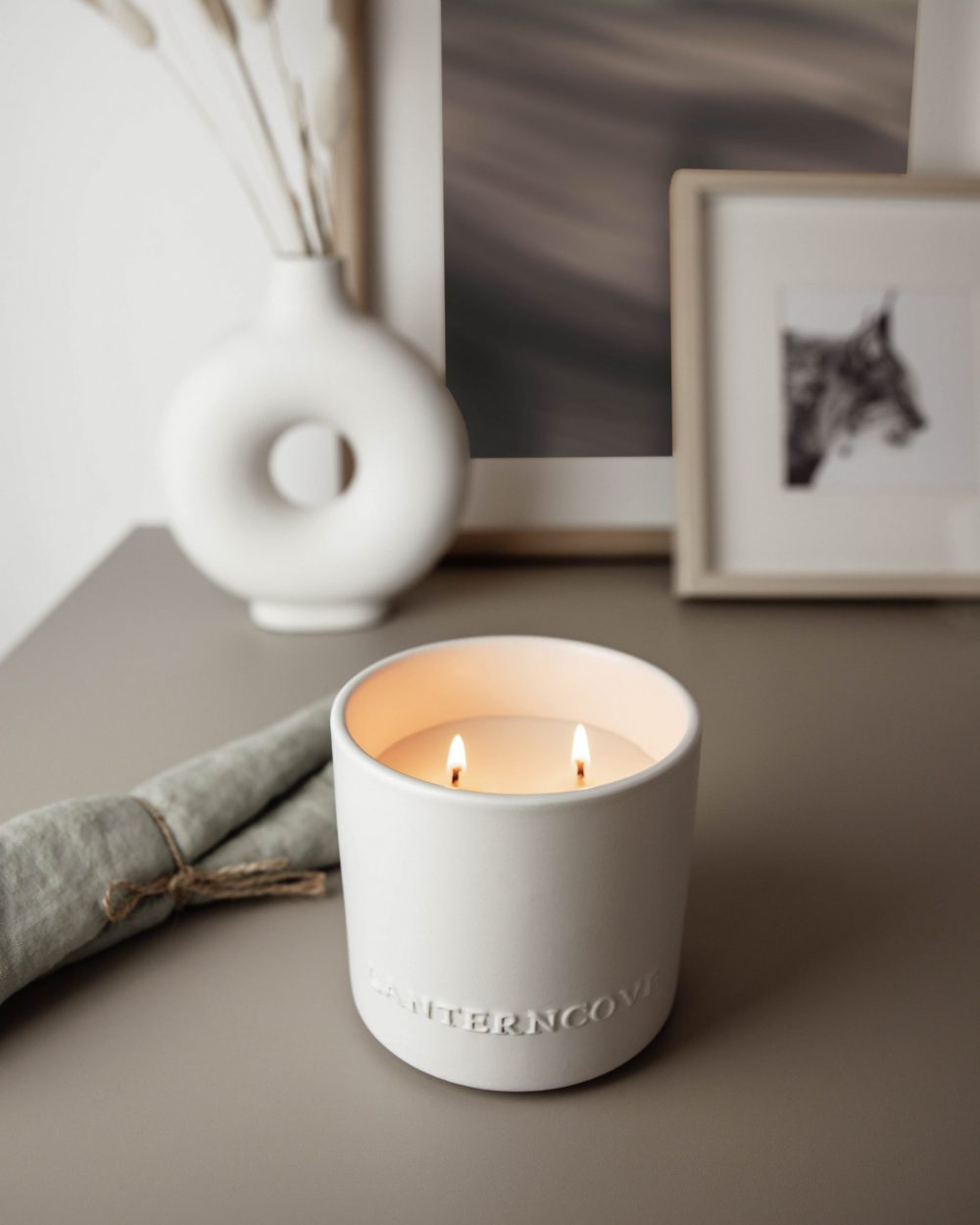 Lantern Cove candle styled with vase and photo frames